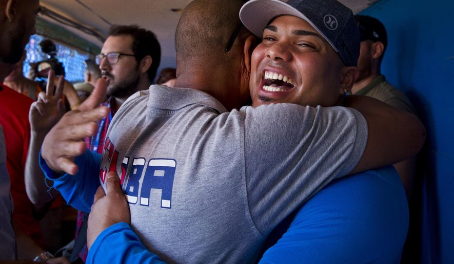 St. Louis Cardinals player Brayan Pena, from Cuba, embraces a former colleague before giving a baseball clinic to children in Havana, Cuba, Wednesday, Dec. 16, 2015. A group of Cuban-born baseball stars once disdained by the island's government for defecting to the United States taught their craft to some of the island's youngest players on Wednesday as part of a triumphant return to Cuba. (AP Photo/Ramon Espinosa)