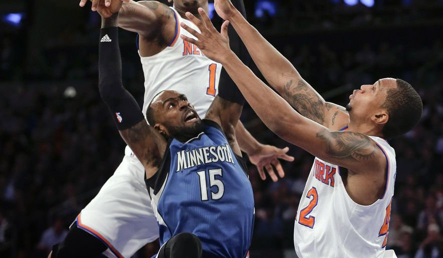 Minnesota Timberwolves forward Shabazz Muhammad (15) puts up a shot against New York Knicks center Kevin Seraphin (1) and forward Lance Thomas (42) during the second quarter of an NBA basketball game Wednesday, Dec. 16, 2015, in New York. (AP Photo/Julie Jacobson)