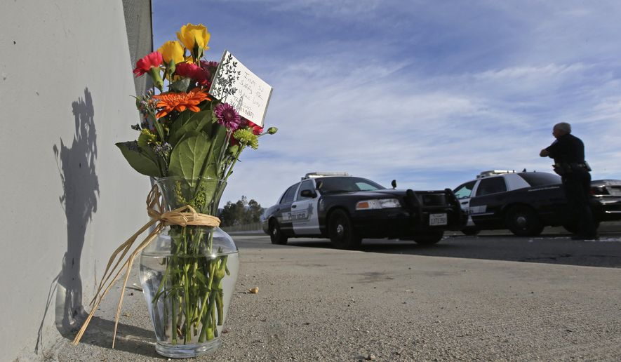 FILE - In this Dec. 3, 2015 file photo, flowers are left by the side of the road as a San Bernardino police officer blocks the road leading to the site of yesterday's mass shooting in San Bernardino, Calif.  President Barack Obama plans to meet with families of victims of the mass shooting in San Bernardino, California, the White House said Wednesday. The meeting is set for Friday. Obama is adding the stop in Southern California to a long-scheduled trip to Hawaii for Christmas vacation. (AP Photo/Chris Carlson, File)