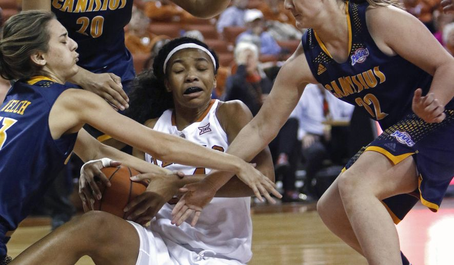 Texas center Imani Boyette, center, tries to control the ball against Canisius' Maria Welch, left, Jasmine Mungo, rear, and Tamara Miskovic, right, during the first half of an NCAA college basketball game Wednesday, Dec. 16, 2015, in Austin, Texas. (AP Photo/Michael Thomas)