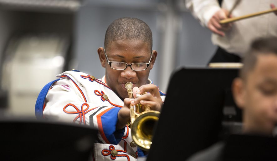 ADVANCE FOR THE WEEKEND OF DEC. 19-20 - In this Thursday, Dec. 10 2015 photo, Raeshaun Potts plays trumpet during band practice at Bartow High School in Bartow, Fla. Even though a birth defect left Potts with two prosthetic legs, he remained undaunted in his determination to stand shoulder to shoulder with his fellow marching band members. (Ernst Peters/The Ledger via AP) MANDATORY CREDIT