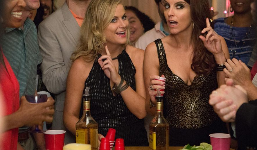 "In this image released by Universal Pictures, Amy Poehler, left, and Tina Fey appear in a scene from the film, ""Sisters."" (K. C. Bailey/Universal Pictures via AP)"