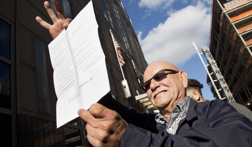 Amaury Villalobos holds up the document showing that his conviction on arson and murder charges was overturned, Wednesday, Dec. 16, 2015, in New York. Villalobos and two other defendants were convicted of arson and six murders after a 1981 trial. Brooklyn District Attorney Ken Thompson asked the judge to clear the men. He says they were convicted based on outdated fire science and a lying witness. (AP Photo/Mark Lennihan)