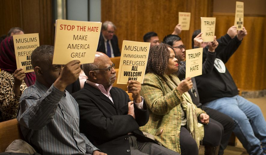 """Demonstrators hold signs voicing their support for a city council resolution Wednesday, Dec. 16, 2015, in St. Paul, Minn., condemning Republican presidential candidate Donald Trump for anti-Muslim, anti-refugee and anti-immigrant speech. The resolution passed by a 6-1 vote Wednesday. Council member Dan Bostrom cast the lone """"no"""" vote. Bostrom says he may not like what Trump says, but he would not try to limit his right to say it. (Aaron Lavinsky/Star Tribune via AP)  MANDATORY CREDIT; ST. PAUL PIONEER PRESS OUT; MAGS OUT; TWIN CITIES LOCAL TELEVISION OUT"""
