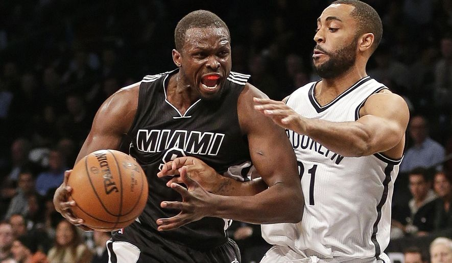 Miami Heat's Luol Deng, left, drives past Brooklyn Nets' Wayne Ellington during the first half of an NBA basketball game Wednesday, Dec. 16, 2015, in New York. (AP Photo/Frank Franklin II)