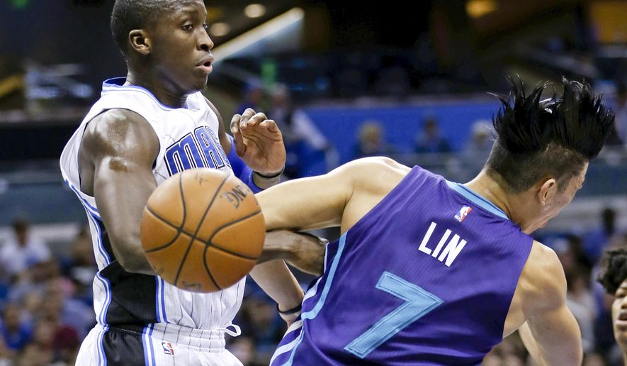 Charlotte Hornets guard Jeremy Lin (7) loses the ball as he collides with Orlando Magic guard Victor Oladipo, left, during the first half of an NBA basketball game Wednesday, Dec. 16, 2015, in Orlando, Fla. (AP Photo/John Raoux)