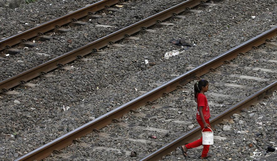 FILE-In this June 30, 2015 file photo,an Indian girl holds a can filled with water and walks past railway tracks to defecate in the open in Mumbai, India. The World Bank has approved a $1.5 billion loan for a sanitation program in India, where millions of people have no access to toilets.The bank said in a statement Wednesday that the loan will be used to support government efforts to provide toilets in villages and end the practice of open defecation by 2019.More than 500 million Indians, especially in rural areas, continue to defecate in the open, despite efforts to encourage people to change their habits. (AP Photo/Rajanish Kakade, file)