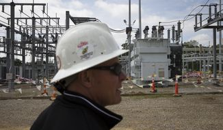 In this Wednesday, May 20, 2015, file photo, Christian Vittorio, an AEP transmission field coordinator, gives a tour of an AEP electrical transmission substation in Westerville, Ohio. (AP Photo/John Minchillo) ** FILE **