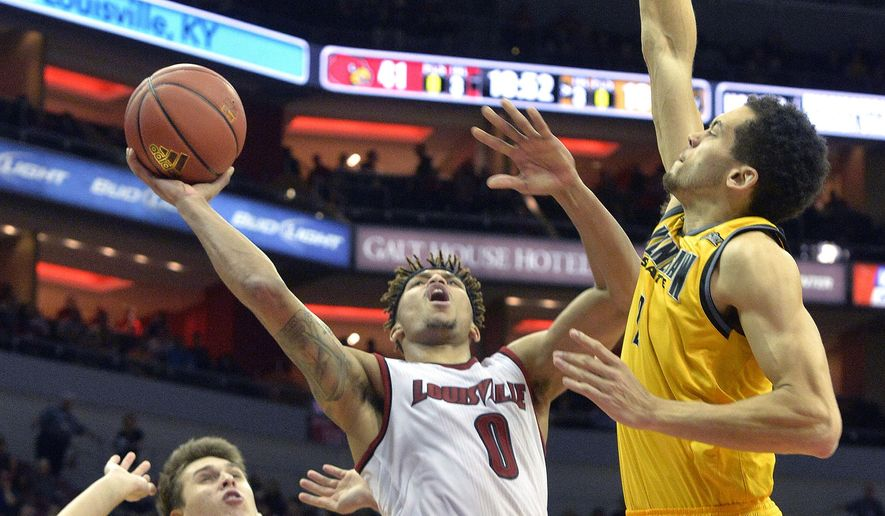 Louisville's Damion Lee (0) attempts a shot between the defense of Kennesaw State's Nick Masterson (21) and Jordan Jones (2) during the second half of an NCAA college basketball game, Wednesday, Dec. 16, 2015, in Louisville, Ky. Louisville won 94-57. (AP Photo/Timothy D. Easley)
