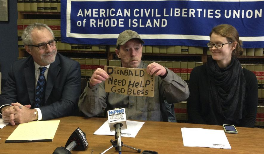 Michael Monteiro, center, with his lawyer Marc Gursky, left, and outreach worker Megan Smith, right, holds the sign that he used  to solicit donations from a median strip in Cranston, R.I., during a news conference Wednesday, Dec. 16, 2015 in Providence, R.I.  Monteiro said he has periodically asked for donations at the intersection for years, but stopped this summer after he was cited by police, then told by a judge not to return. Monteiro is now suing the city for violating his constitutional rights. (AP Photo/Michelle R. Smith)