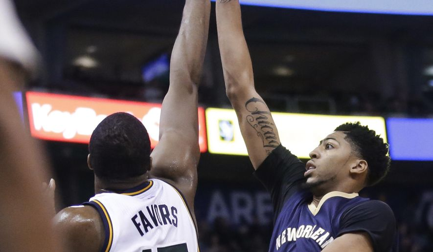 New Orleans Pelicans forward Anthony Davis, right, shoots as Utah Jazz forward Derrick Favors (15) defends during the second quarter of an NBA basketball game Wednesday, Dec. 16, 2015, in Salt Lake City. (AP Photo/Rick Bowmer)