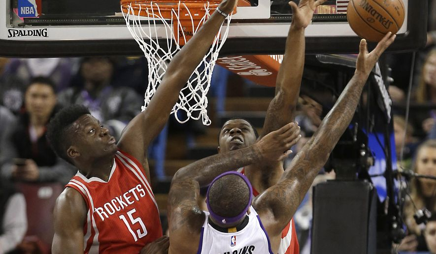 Sacramento Kings forward DeMarcus Cousins, right front, goes to the basket against Houston Rockets' Clint Capela, left, and Terrence Jones during the first quarter of an NBA basketball game in Sacramento, Calif., Tuesday, Dec. 15, 2015.(AP Photo/Rich Pedroncelli)