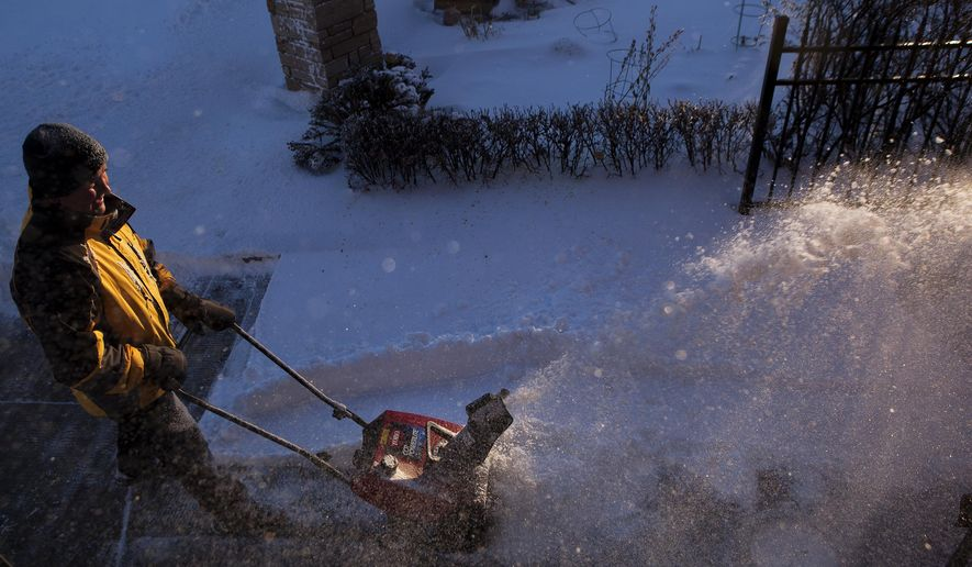 Marcus Flavin plows a sidewalk early Wednesday, Dec. 16, 2015, at the Emmanuel Episcopal Church in Rapid City, S.D., after a winter storm dropped roughly six inches of snow overnight and caused power outages and school closures. (Josh Morgan/Rapid City Journal via AP) TV OUT; MANDATORY CREDIT