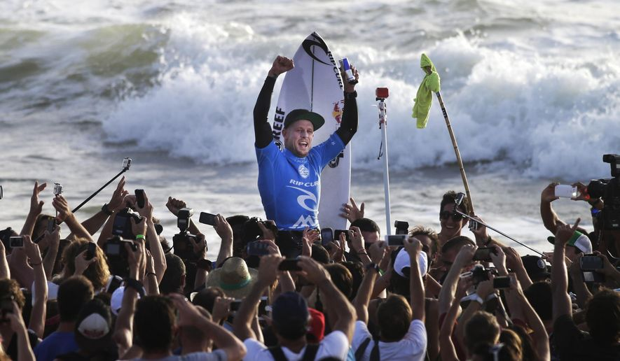 FILE - In this Oct. 20, 2014 file photo, Australian surfer Mick Fanning celebrates after winning the Moche Rip Curl Pro Portugal surf contest in Supertubos beach, Peniche, central coast of Portugal. Mick Fanning, who survived a shark attack in South Africa in July, decided to keep competing at the Pipeline Masters in Hawaii to pursue his fourth world surfing title despite learning of the death of his brother on Wednesday, Dec. 16, 2015. (AP Photo/Francisco Seco, File)