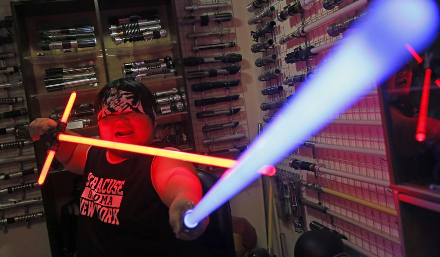 """In this Dec. 14, 2015, photo, 32-year-old Tsai Jung-chou, also known as """"Makoto Tsai"""", poses with his handcrafted replicas of the Star Wars lightsaber at his home workshop in New Taipei City, Taiwan. A former optical engineer, Tsai now designs and fabricates his own versions of the iconic sci-fi weapon which he sells for up to $400 per model. (AP Photo/Wally Santana)"""