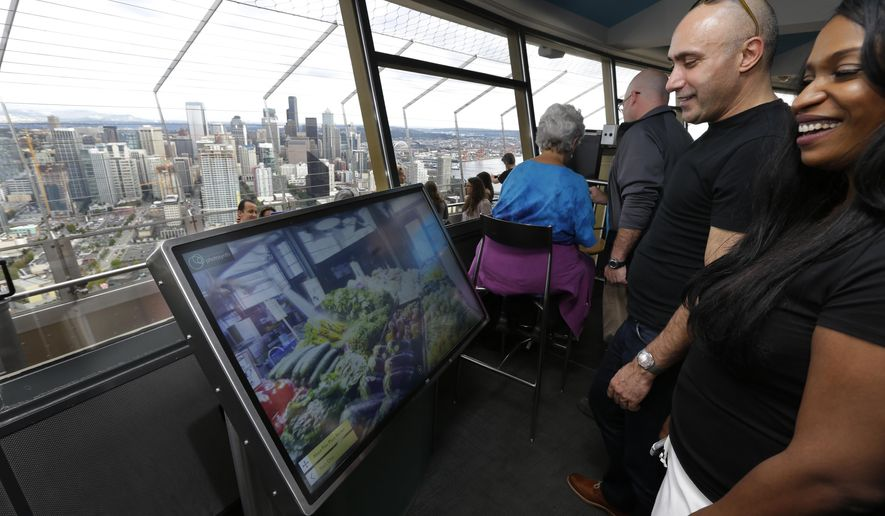 FILE - In this Sept. 19, 2014, file photo, Anan Bishara, left, and Denise Burrell, right, both from New York, check out a virtual reality display that lets visitors explore the Pike Place Market and other attractions atop the Space Needle in Seattle. The high-tech attractions are part of an explosion of virtual reality in the travel industry. (AP Photo/Ted S. Warren, File)