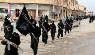 This undated file image posted on a militant website on Tuesday, Jan. 14, 2014, which has been verified and is consistent with other AP reporting, shows fighters from the al Qaida linked Islamic State of Iraq and the Levant (ISIL), now called the Islamic State group, marching in Raqqa, Syria. (AP Photo/Militant Website, File)
