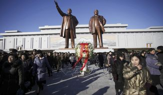 North Koreans bring floral tributes to Mansu Hill, where bronze statues of their late leaders Kim Jong Il and his father Kim Il Sung, stand, Thursday, Dec. 17, 2015, in Pyongyang, North Korea. Thousands visited the site to mark the fourth anniversary of Kim Jong Il's death. (AP Photo/Jon Chol Jin)