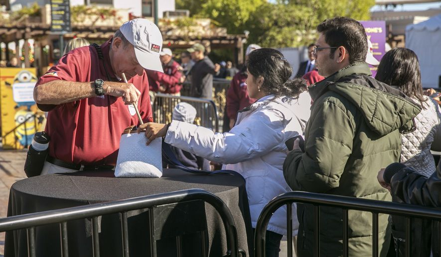 Guests' bags are screened for additional security measures at Universal Studios in Los Angeles on Thursday, Dec. 17, 2015. Officials at Universal, Disney and SeaWorld's Florida theme parks say they are adding enhanced security measures, including metal detectors, inside and outside of venues ahead of the busy holiday season. (AP Photo/Damian Dovarganes)