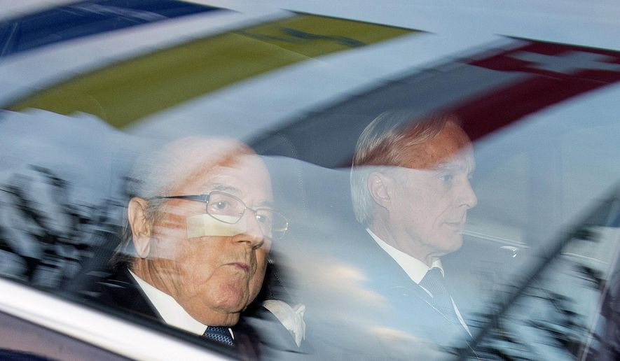 """FIFA President Sepp Blatter, left, and his lawyer Lorenz Erni, right, arrive in a car at the FIFA headquarters """"Home of FIFA"""" in Zurich, Switzerland, Thursday morning, Dec. 17, 2015. While FIFA President Joseph S. Blatter will appear in person on Thursday before the panel of four judges of the FIFA ethics court, UEFA President Michel Platini plans to boycott his hearing on Friday 18 December. Blatter and Platini were banned for 90 days for all activities in football.  (Walter Bieri/Keystone via AP)"""