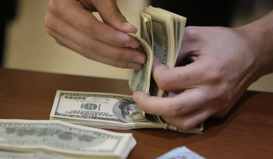 A customer counts U.S. dollars after buying them at an illegal exchange location in Buenos Aires, Argentina, Thursday, Dec. 17, 2015. Argentina's currency sharply devalued against the U.S. dollar on Thursday as the new administration lifted deeply unpopular limits on the buying of foreign currencies. (AP Photo/Victor R. Caivano)