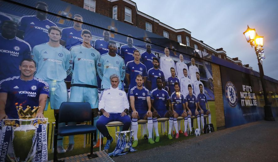"""A poster showing former Chelsea manager Jose Mourinho, centre with cup at his feet, with the soccer team outside Chelsea's Stamford Bridge stadium in London, Thursday, Dec. 17, 2015.  Jose Mourinho's second spell as Chelsea manager ended Thursday, only seven months after he won his third Premier League title with the club, as Chelsea soccer team released a statement saying it has """"parted company"""" with Mourinho.(AP Photo/Kirsty Wigglesworth)"""
