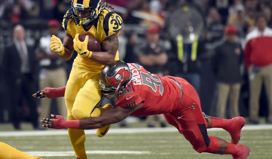 St. Louis Rams running back Todd Gurley, left, runs with the ball as Tampa Bay Buccaneers defensive end William Gholston tries to make the tackle during the second quarter of an NFL football game on Thursday, Dec. 17, 2015, in St. Louis. (AP Photo/L.G. Patterson)