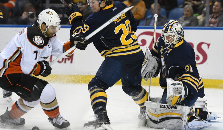 Anaheim Ducks left winger Andrew Cogliano (7) battles for the puck with Buffalo Sabres defenseman Jake McCabe (29) as goaltender Chad Johnson (31) defends during the second period of an NHL hockey game, Thursday Dec. 17, 2015 in Buffalo, N.Y. (AP Photo/Gary Wiepert)