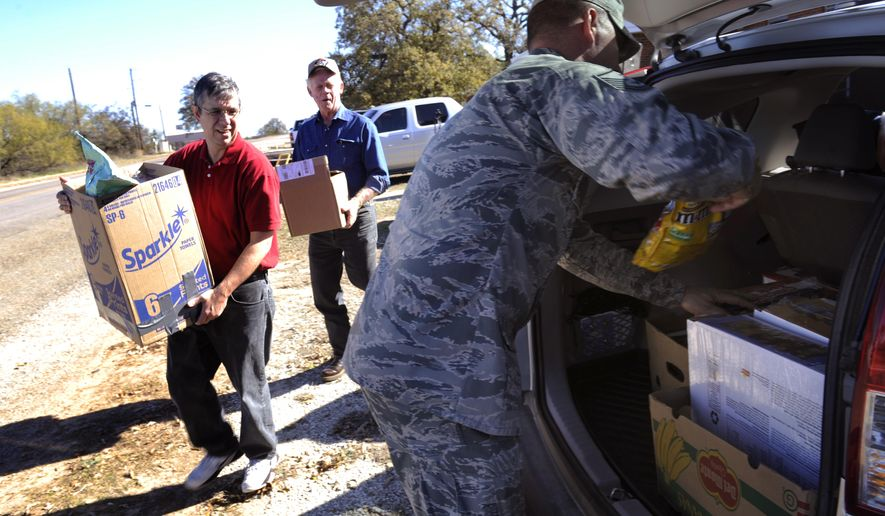 ADVANCE FOR USE MONDAY, DEC. 21 - In this photo taken Tuesday, Dec. 8, 2015, Brad Slaten, left, and Paul Motley carry boxes of gifts to a the back of a vehicle in Novice, Texas. Master Sgt. Eric Siemsen organizes the items which were taken to Dyess Air Force base to be distributed to members serving overseas. (Ronald W. Erdrich/The Abilene Reporter-News via AP) MANDATORY CREDIT