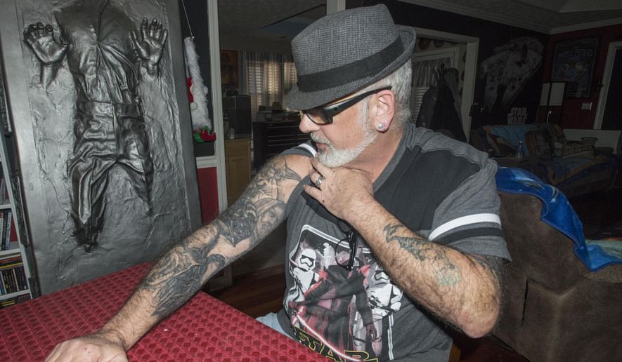 "In this photo taken Monday, Dec. 14, 2015, Mike Avallone shows his collection of Star Wars tattoos at his home in Deatsville, Ala. He and his wife Kelly Avallone live in a Star Wars themed home and are anxiously awaiting this week's release of  ""Star Wars: The Force Awakens.""(Shannon Heupel/The Montgomery Advertiser via AP)  NO SALES; MANDATORY CREDIT"