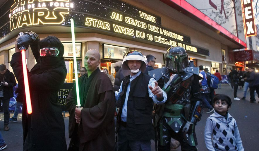 """People dressed in character pose outside the Grand Rex movie theater for photographers prior to a screening of """"Star Wars: The Force Awakens""""in Paris, Wednesday, Dec. 16, 2015. (AP Photo/Michel Euler)"""
