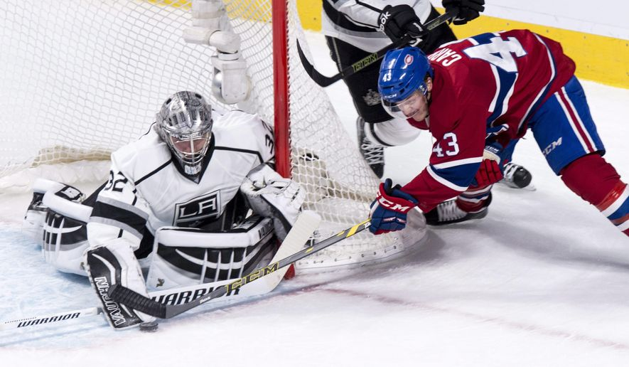 Los Angeles Kings' goalie Jonathan Quick (32) stops Montreal Canadiens' Daniel Carr (43) as he tries to score on the wrap around during second period NHL hockey action, in Montreal, on Thursday, Dec. 17, 2015. (Paul Chiasson/The Canadian Press via AP)