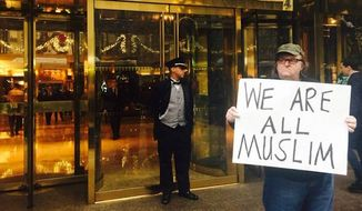 """Michael Moore stood in front of Trump Tower in New York City holding a sign declaring, """"We are all Muslim,"""" in the wake of Donald Trump's controversial proposal to temporarily halt Muslim immigrants from entering the country. (Twitter/@MMFlint)"""