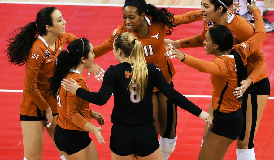 Texas players, including Chiaka Ogbogu (11), celebrate a point against Minnesota during an NCAA women's volleyball tournament semifinal in Omaha, Neb., Thursday, Dec. 17, 2015. (AP Photo/Nati Harnik)