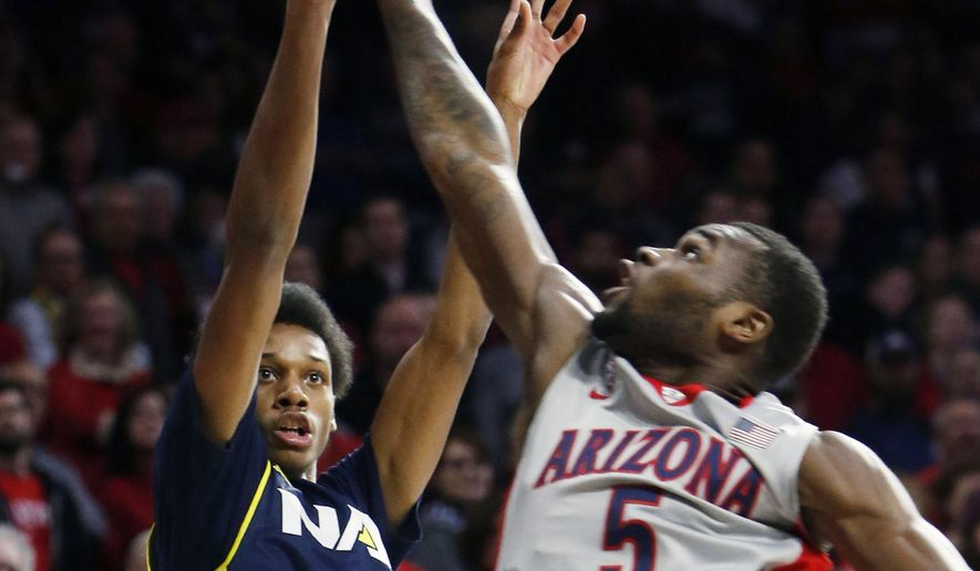 Northern Arizona guard Marcus DeBerry (41) shoots in front of Arizona guard Kadeem Allen during the first half of an NCAA college basketball game, Wednesday, Dec. 16, 2015, in Tucson, Ariz. (AP Photo/Rick Scuteri)
