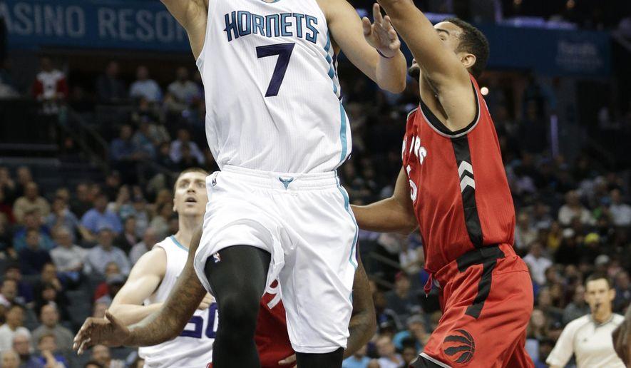 Charlotte Hornets' Jeremy Lin (7) drives past Toronto Raptors' Cory Joseph (6) during the first half of an NBA basketball game in Charlotte, N.C., Thursday, Dec. 17, 2015. (AP Photo/Chuck Burton)