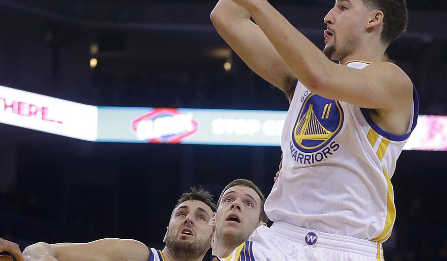 Golden State Warriors' Klay Thompson, right, shoots over Phoenix Suns' Jon Leuer during the first half of an NBA basketball game Wednesday, Dec. 16, 2015, in Oakland, Calif. (AP Photo/Ben Margot)