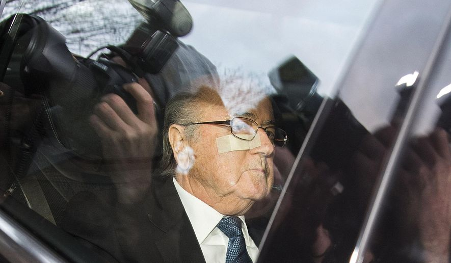 "FIFA President Sepp Blatter arrives in a car at the FIFA headquarters ""Home of FIFA"" in Zurich, Switzerland, Thursday morning, Dec. 17, 2015. (Walter Bieri/Keystone via AP)"