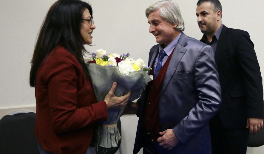 Syrian refugee Refaai Hamo, center, is greeted by Michigan State Rep. Rashida H. Tlaib at a news conference, Thursday, Dec. 17, 2015, in Romulus, Mich. The Syrian scientist whose harrowing, tragic story spurred supporting words from President Barack Obama and a fundraising effort by actor Edward Norton has arrived as a refugee with his family in the Detroit area. (AP Photo/Carlos Osorio)
