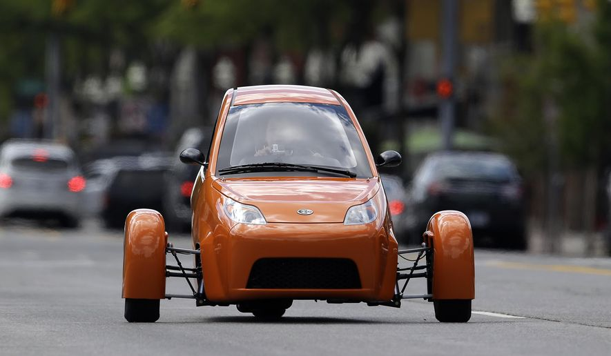 FILE - In this Aug. 14, 2014 file photo, the Elio, a three-wheeled prototype vehicle, is shown in traffic in Royal Oak, Mich. Utah lawmakers plan to set safety and licensing rules next year for new, alternative three-wheeled vehicles such as the Elio, that resemble motorcycles but operate like cars. Autocycles have barely begun showing up on Utah roads, but state Rep. Stewart Barlow, R-Fruit Heights, said the state needs to have rules in place before the unconventional vehicles become commonplace as manufacturers start rolling them out in force.(AP Photo/Paul Sancya, File)