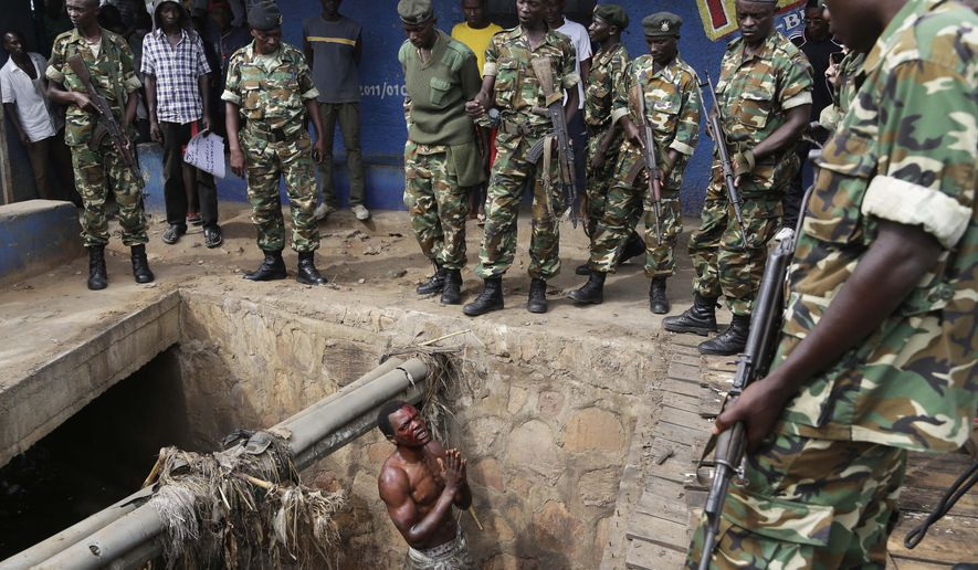 FILE -Jean Claude Niyonzima, a suspected member of the ruling party's Imbonerakure youth militia, pleads with soldiers to protect him from a mob of demonstrators after he came out of a sewer  in the Cibitoke  district of Bujumbura, Burundi, Thursday, May 7, 2015. (AP Photo/Jerome Delay, File)