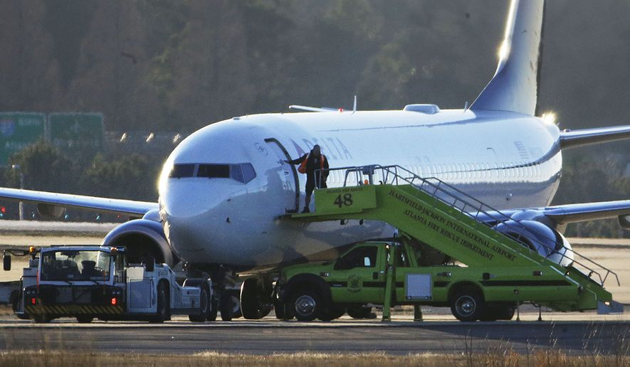 A worker closes the door to a Delta Airlines airplane sitting on the tarmac at Hartsfield-Jackson Atlanta International Airport in Atlanta on Jan. 24, 2015. (Associated Press) **FILE**