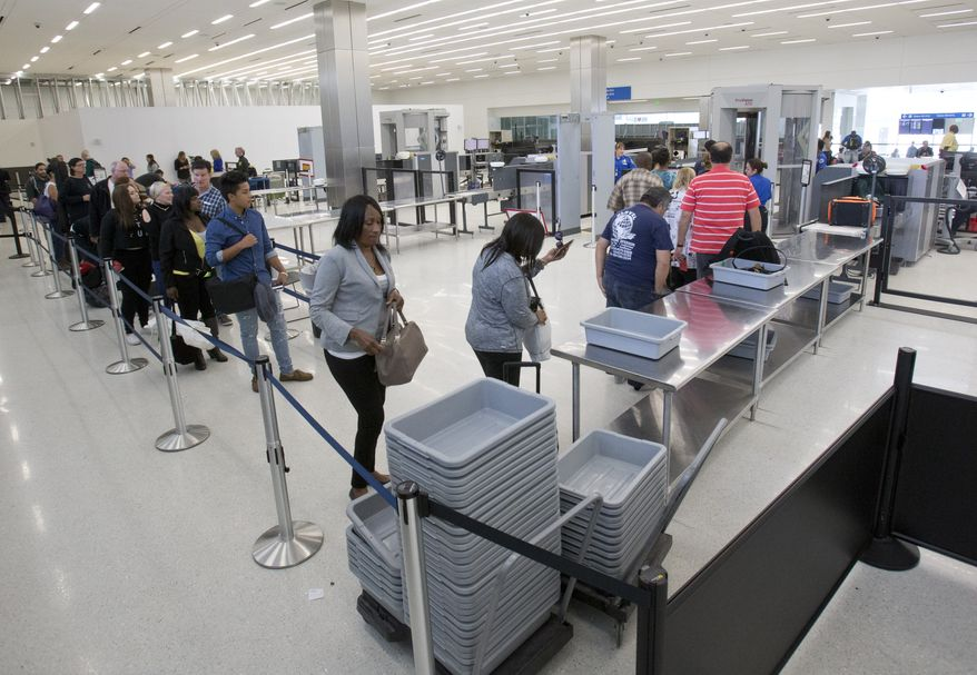 Passengers load their items into bins as they pass through security before flying out of the Fort Lauderdale-Hollywood International Airport, Friday, Dec. 18, 2015, in Fort Lauderdale, Fla. Transportation Security Administration spokesperson Sari Koshetz said that about 8,000 lbs. of prohibited items were confiscated this year by the TSA at the Fort Lauderdale airport. (AP Photo/Wilfredo Lee)