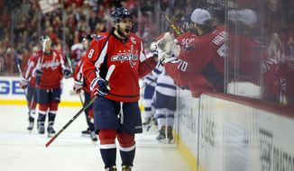 Washington Capitals left wing Alex Ovechkin (8), from Russia, high fives goalie Braden Holtby (70), as he reacts after the Capitals scored against the Tampa Bay Lightning during the third period of a hockey game at the Verizon Center in Washington on Friday, Dec. 18, 2015. After turning the game around in the third period the Capitals won 5-3. (AP Photo/Jacquelyn Martin)