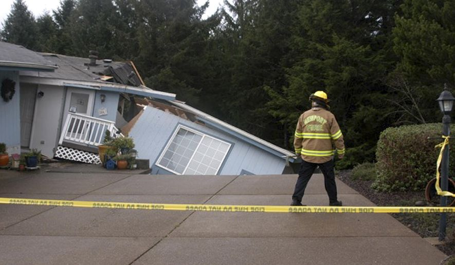 In this Friday, Dec. 18, 2015 photo released by the Newport News-Times, a Newport Firefighter looks at a home that was damaged from storms in Newport, Ore. Fresh storms barreled through the already sodden Pacific Northwest on Friday, triggering a landslide that killed a woman near the Oregon Coast and clogging mountain passes in the Washington Cascades. (Steve Card/Newport News-Times via AP) MANDATORY CREDIT