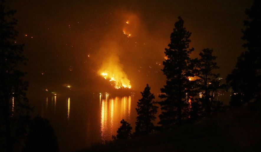File - In this Aug. 17, 2015 file photo, timber burns in the First Creek fire near lakeside structures on the western shore of Lake Chelan near Chelan, Wash. The U.S. Forest Service depleted its firefighting budget in August as the costliest fire season in U.S. history destroyed hundreds of homes in California and the Pacific Northwest. (AP Photo/Ted S. Warren, file)