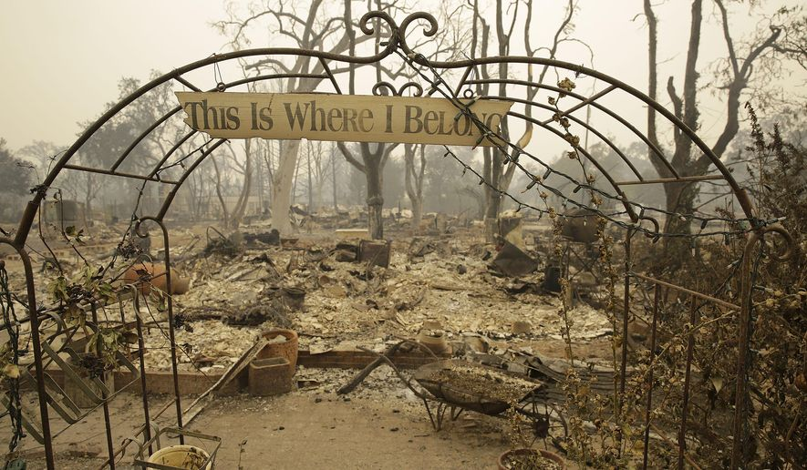 FILE -- In this Sept. 13, 2015 file photo, a sign hangs above an entryway to a home destroyed by fire in Middletown, Calif.  Gov. Jerry Brown's administration estimates it will cost at least $243 million to clean up and remove debris left in the wake of two major Northern California wildfires this fall. (AP Photo/Eric Risberg, File)