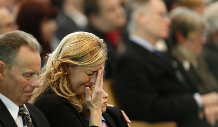 Julie Capuano the wife of Chicago firefighter Daniel Capuano, grieves at his funeral at St. Rita High School's chapel in Chicago on Friday, Dec. 18, 2015.  Capuano died after falling down an elevator shaft while battling a warehouse fire Monday, Dec. 14. (Jose Osorio/Chicago Tribune via AP, Pool)