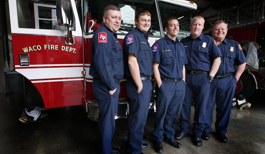In a Tuesday, Dec. 15, 2015 photo, Waco fireman who are related to each other gather near one of the fire trucks, in Waco, Texas. The group will celebrate Christmas at different times due to their shifts at the department.  Left to right are David Maness, Tyler Bullard, Adam Nystrom, Brian Westerfield and Mike Westerfield  The group has about 70 years of collective service among them. (Rod Aydelotte/Waco Tribune Herald, via AP)