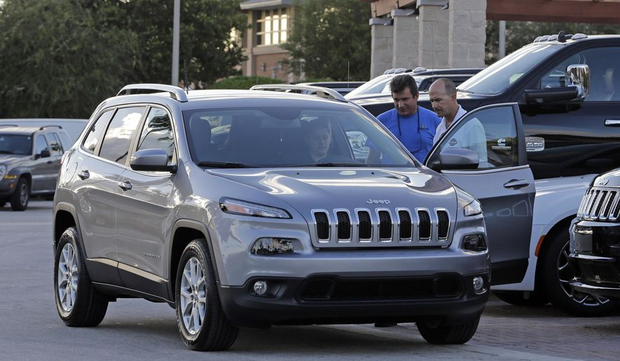 In this photo taken Thursday, Nov. 5, 2015, salesperson Jerry Camero, right, delivers a 2016 Jeep Cherokee Limited to a customer at a Fiat Chrysler dealer in Doral, Fla. Fiat Chrysler is recalling nearly 56,000 Jeep Cherokee SUVs worldwide to fix a water leak that can cause an electrical short in the power tailgates. The recall covers Cherokees from the 2015 and 2016 model years. Water can get into the tailgate control module, increasing the risk of a fire. The company says no fires or injuries have been reported. (AP Photo/Alan Diaz)
